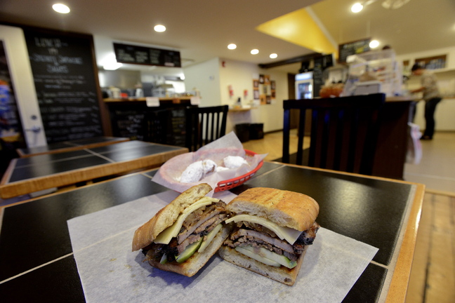 The roasted pork loin sandwich at St. Joe's is stuffed with pork, caramelized onions, crisp apples and sharp cheddar cheese. Behind is an order of Bennies – a version of beignets, covered in powdered sugar. St. Joe's Coffee in Scarborough has creative fare at better than fair prices.