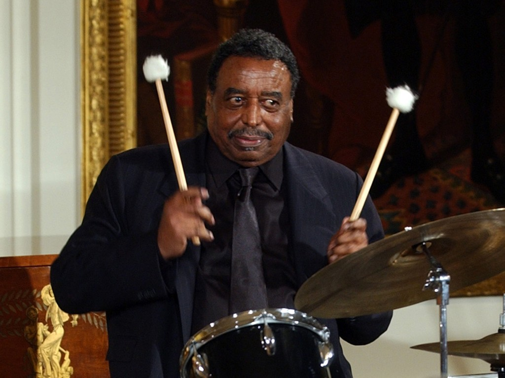 This 2004 photo shows Chico Hamilton, a recipient of the National Endowment for the Arts Jazz Masters Fellowship, performing a drum solo in the East Room of the White House during a reception to honor Black Music Month.