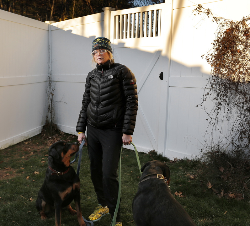 Toni Macquinn stands with her dogs, Sailor and Marina, in the backyard of her Old Orchard Beach home Wednesday, in the same spot where she says she was nearly hit by stray bullets from a hunter's rifle.