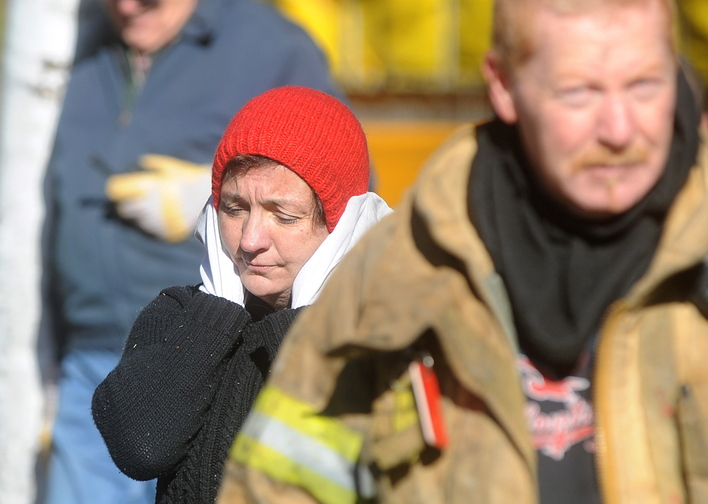 Laura Ellis reacts after she escaped injury when her car caught fire and spread to the trailer she was staying in on Beach Road in South China on Tuesday morning.
