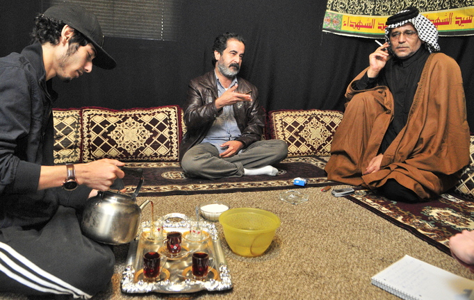Youssof Zamat, left, pours tea while Ghazi Yousif, center, answers questions during an interview at the apartment of Khalid Zamat, right, in Augusta.