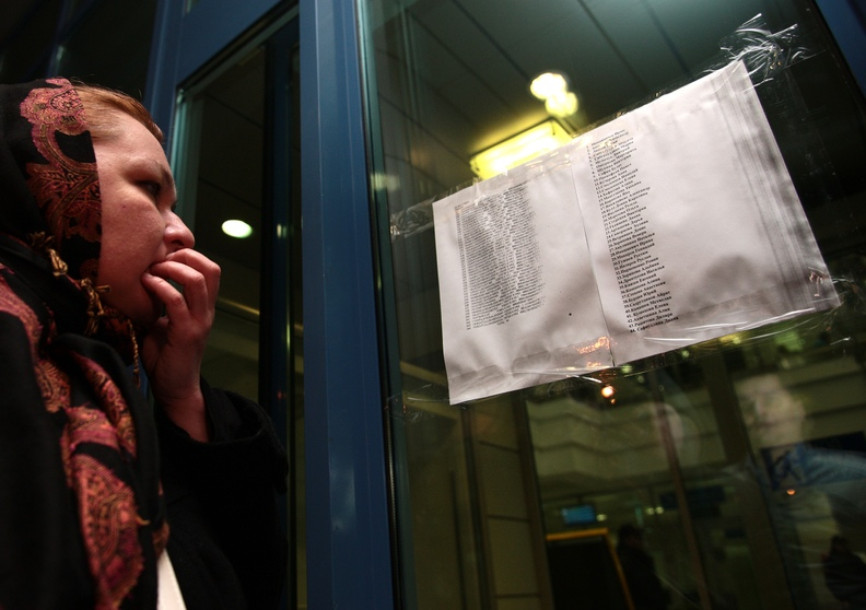 A woman reads a list with the names of passengers who were aboard an airliner that crashed in Kazan on Sunday.