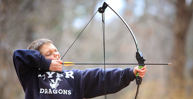 Emerson Dolan, 9, takes aim while practicing archery with his dad, Ryan, at their home in Cape Elizabeth.