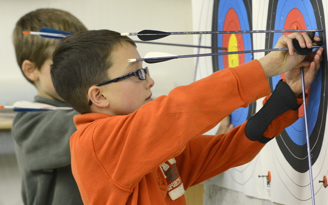 Jonathan Dalessandro, 9, of Westbrook removes arrows from his target during practice at the Lakeside Archery shop in North Yarmouth.