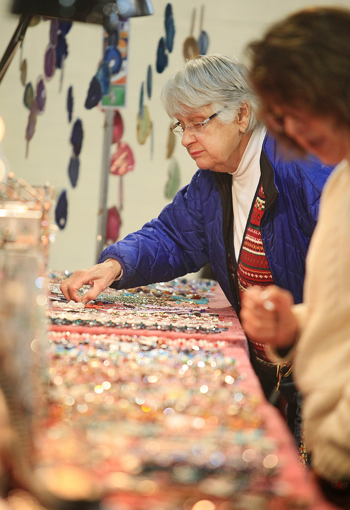 June O'Donnell of Gray looks at pieces of hand-crafted jewelry created by Crafty Scotts in Sabattus while shopping Sunday with friend Gailyn Doucette-Coons, also of Gray.