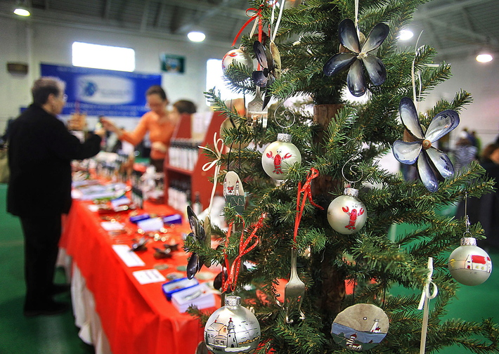 Handcrafted ornaments with Maine motifs, made by Tina Quattrucci of Saco, attract shoppers at a holiday craft fair at the Stevens Avenue Armory in Portland on Sunday.