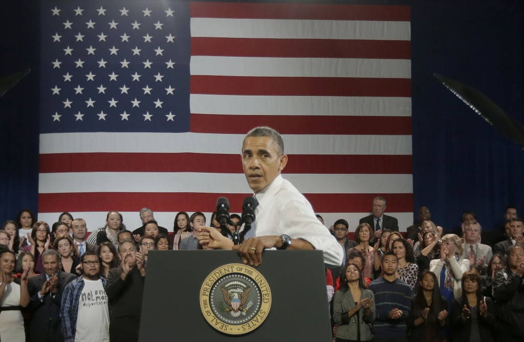 President Obama turns around to respond to a heckler interrupting his speech about immigration reform Monday in San Francisco. The heckler, who urged the president to stop deportations, was allowed to remain in the audience.