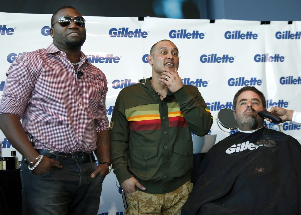 Boston police Officer Steve Horgan is shaved as Red Sox players David Ortiz, left, and Shane Victorino, center, look on during a shave-off for One Fund Boston, the Boston Marathon charity for bombing victims, in Boston on Monday.