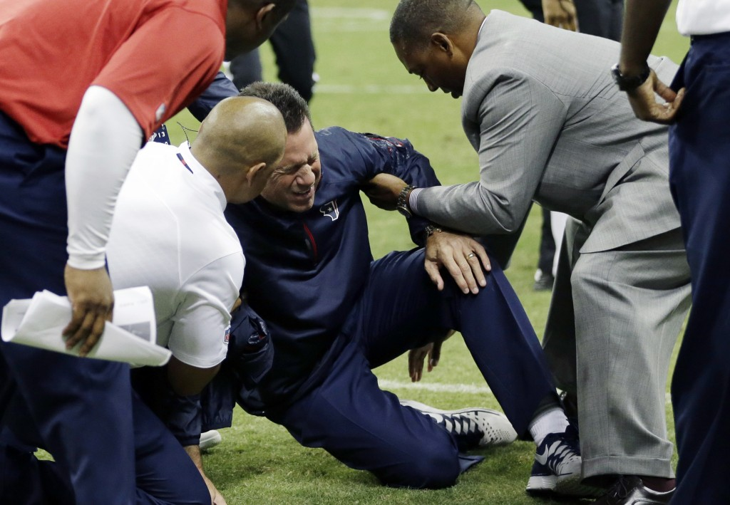 Houston Texans head coach Gary Kubiak, center, is helped after he collapsed on the field during the second quarter of a game against the Indianapolis Colts on Sunday in Houston.