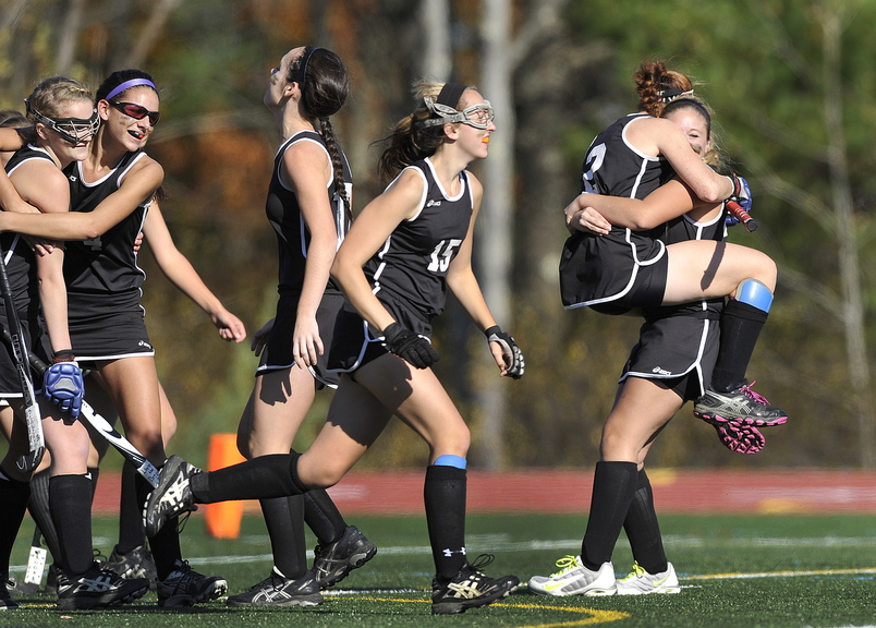 Skowhegan's Renee Wright, (2) and Emily Trial, (23) embrace at far right as they celebrate their victory over Scarborough during the Class A field hockey championship at Yarmouth High School Saturday, November 2, 2013.