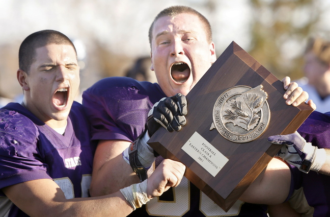 Cody O'Brien, left, and Greg Grinnell – the Cheverus High captains – celebrate with the Eastern Class A championship trophy Saturday after the Stags rallied to a 22-19 victory at home against Portland, earning a berth in the state final against Bonny Eagle.