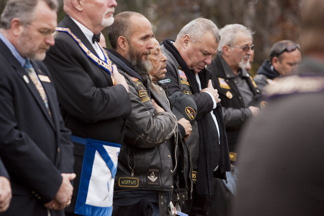 Attendants reflect in prayer during the second annual Veterans Day observance at Pine Grove Cemetery in West Kennebunk on Sunday.