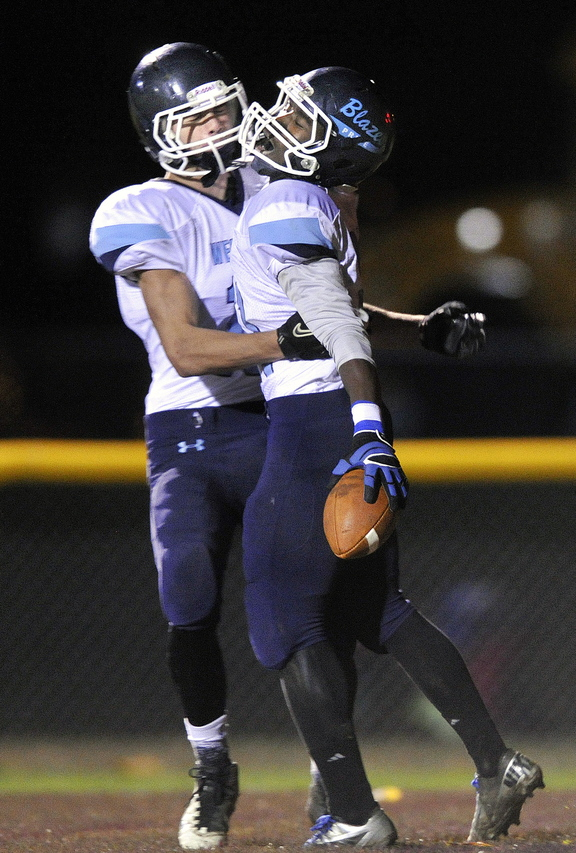Westbrook's Derek Breunig, left, hugs teammate Maurice Johnson after Johnson's first half touchdown Friday night.