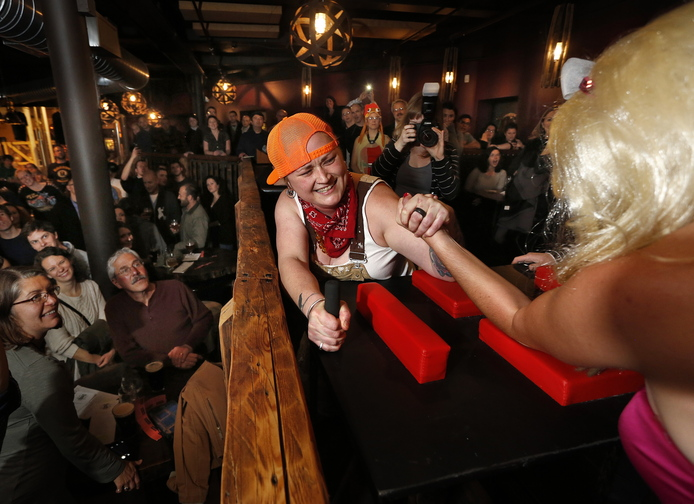 "Derek Davis/Staff Photographer: Kate Squibb, aka ""Lumber Smack Sally"" of Portland reaches for more as she tries to defeat ""Barrel Roll Barbie"" during an arm wrestling fundraiser at In'finiti. Photographed on Thursday. November 7, 2013."