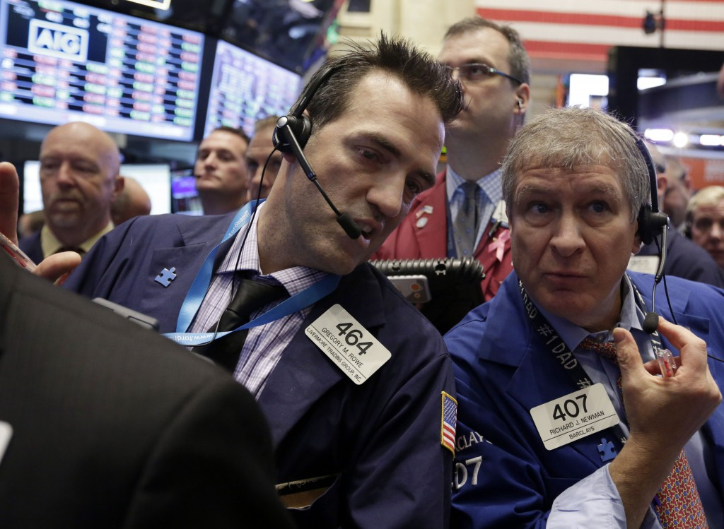 Traders Gregory Rowe, left, and Richard Newman confer on the floor of the New York Stock Exchange on Wednesday.