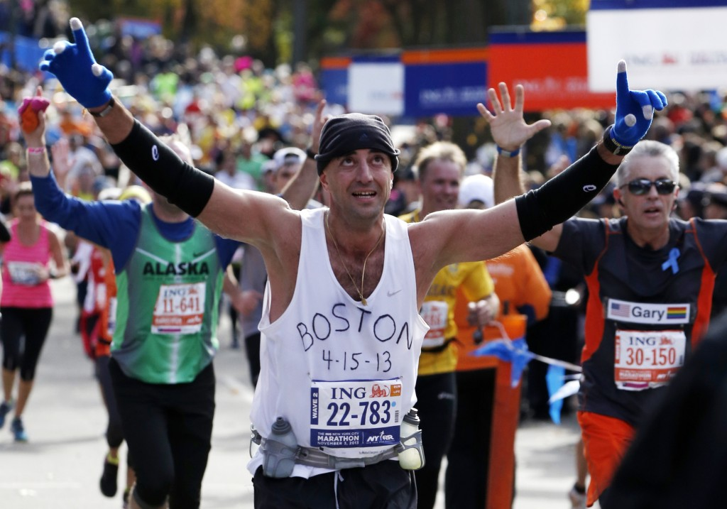 Wearing a shirt that pays tribute to victims of the Boston Marathon bombings, Andrew Mangone of the United States reacts crossing the finish line after completing the New York City Marathon, Sunday, Nov. 3, 2013, in New York.