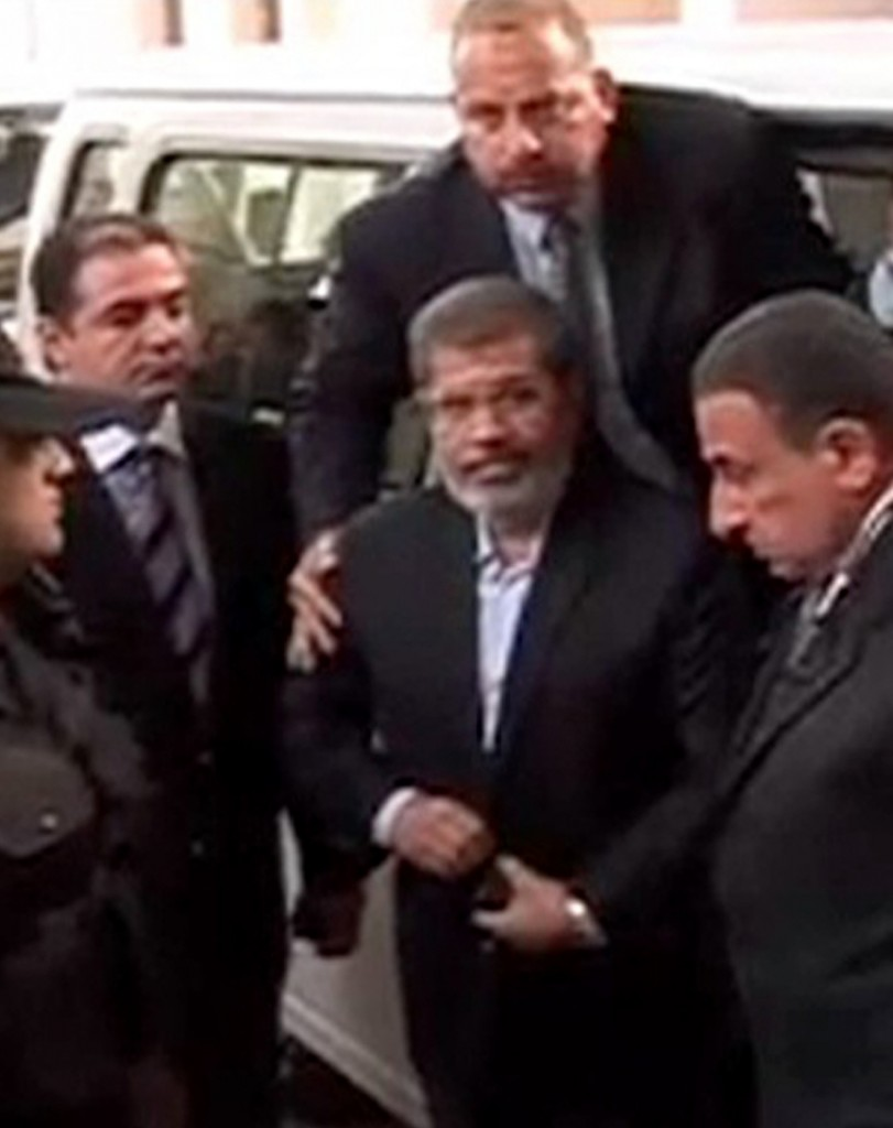 This image made from video provided by Egypt's Interior Ministry shows ousted President Mohammed Morsi, center, arriving for a trial hearing in Cairo on Monday.