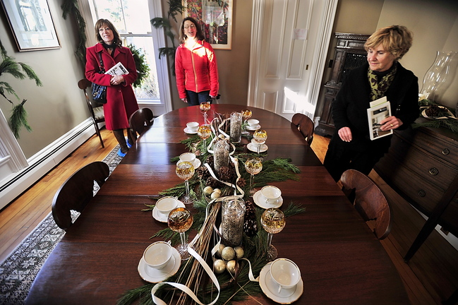 Patricia Neja, from left, Suzanne Ambler and Allie Libby view a centerpiece made by Amy Young Pierce during the Holiday Home Tour in Portland on Saturday.