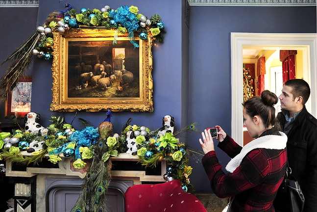 With her boyfriend, Dan Brown of Portland, Samantha Poquette of Wells takes a photo of a mantel in a house owned by Dan Kennedy and his partner, John Hatcher, on the Holiday Home Tour in Portland's West End on Saturday.