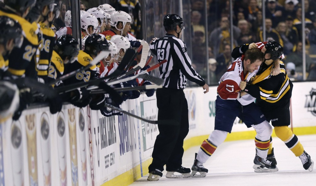 Teammates watch as Florida Panthers center Jesse Winchester and Boston Bruins center Gregory Campbell tangle during the first period of Thursday night's game in Boston. Both players received major penalties for fighting, and the Bruins won to snap a minor slump.