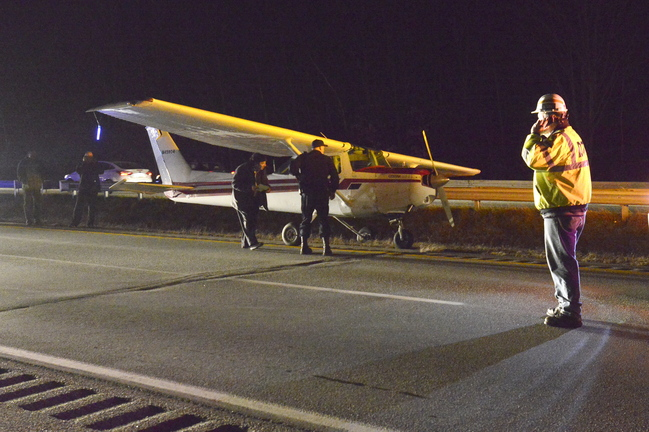 State police and state transportation officials inspect the small plane that made an emergency landing on I-295 Thursday.