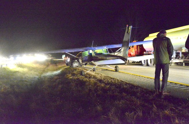 Sachin Hejaji of Falmouth talks on his phone after landing a Cessna 152 in the southbound lanes of Interstate 295 in Cumberland on Thursday evening. Drivers who saw the plane gliding low apparently slowed down, creating a gap in which he landed safely.