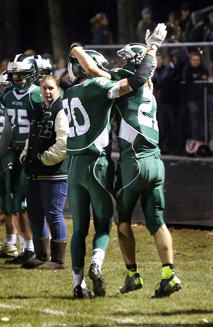 Ben Malloy, left, and Jon Woods of Bonny Eagle celebrate Friday night after Woods dove into the end zone for the only score of the first half against Thornton Academy.