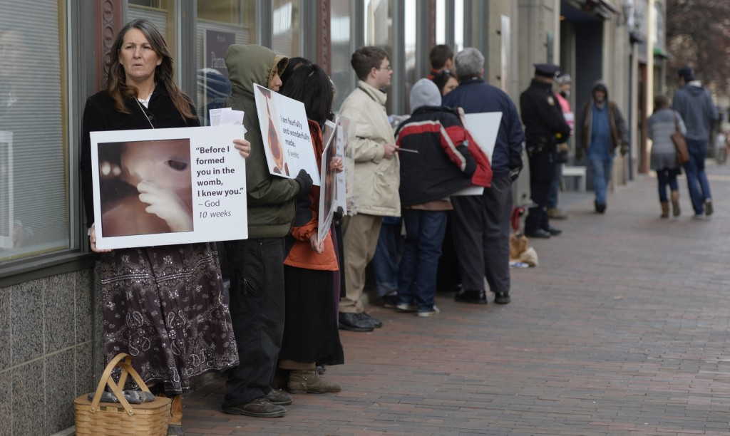 Leslie Sneddon of Richmond protests outside Planned Parenthood on Congress Street in Portland on Friday.