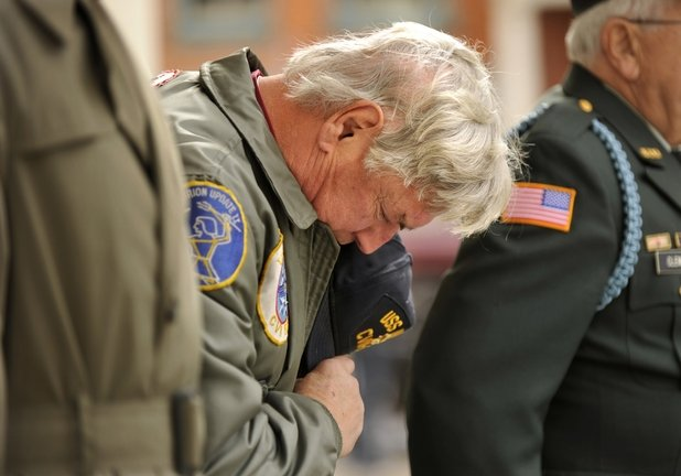 Michael Young of Bellefonte, Pa., a retired Navy lieutenant commander, bows his head Monday during a Veterans Day ceremony outside the Centre County Courthouse in Bellefonte. The federal Department of Veterans Affairs has set a 2015 deadline for eliminating the backlog of disability claims, but it has a long way to go to reach its goal.