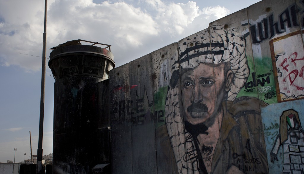 A man walks past a section of the separation barrier with graffiti depicting the late Palestinian leader Yasser Arafat in the West Bank city of Ramallah on Friday, nearly nine years after Arafat's death.