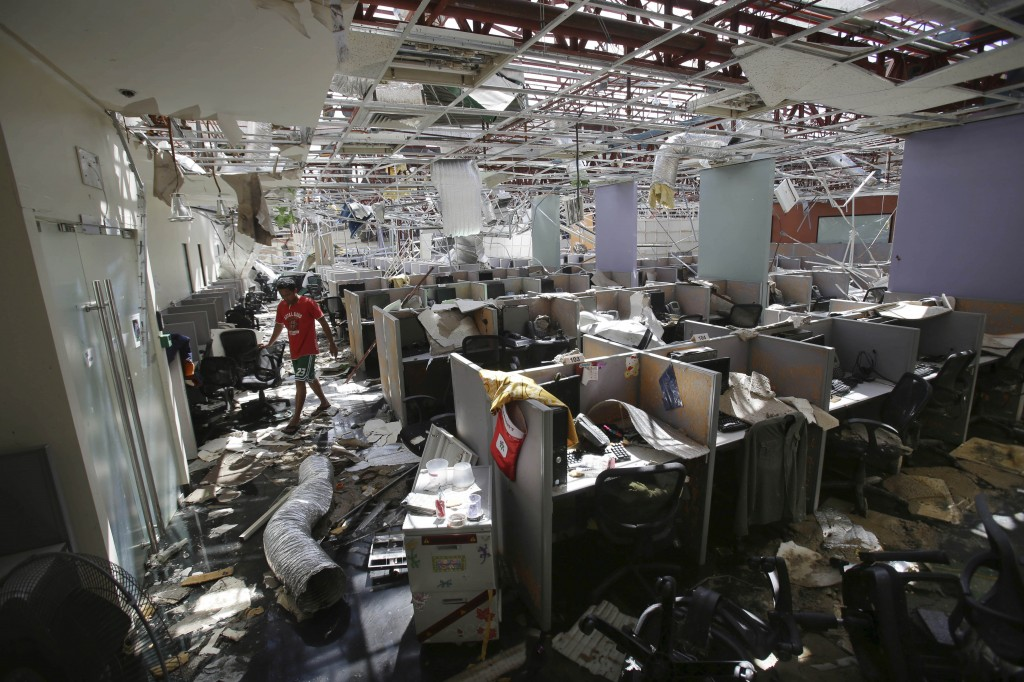 A worker walks inside a damaged call center office in Palo town, Leyte province, central Philippines Tuesday, Nov. 19, 2013. More than 4 million people have been displaced and need food, shelter and water after Typhoon Haiyan hit the country on Nov. 8.