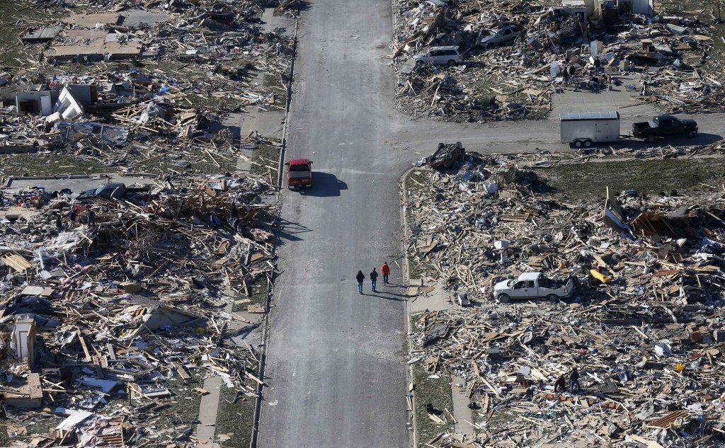 People walk down a street amid tornado devastatation Monday in the western Illinois town of Washington. It was one of the worst-hit areas after intense storms and tornadoes swept through Illinois on Sunday. The National Weather Service says the tornado that hit Washington had a preliminary rating of EF-4, meaning wind speeds of 170-190 mph.