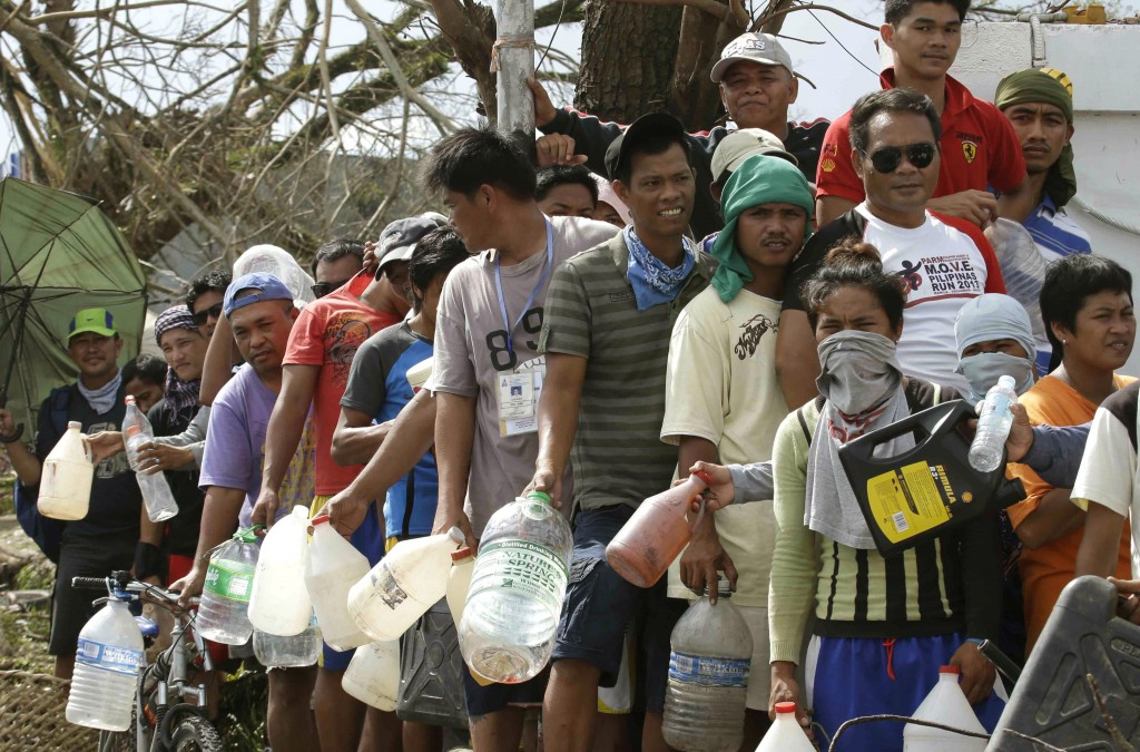 Typhoon survivors line up to get fuel from an abandoned filling station Thursday in Tacloban city in central Philippines. Aid has been slow to reach the people displaced by the storm that tore across several islands in the eastern Philippines last Friday.