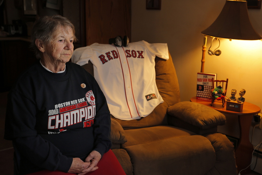 Patricia Kennedy sits in her living room Thursday next to where her late husband, James, often watched his beloved Red Sox play baseball. He died Tuesday, so the family placed the jersey there for Wednesday's game.