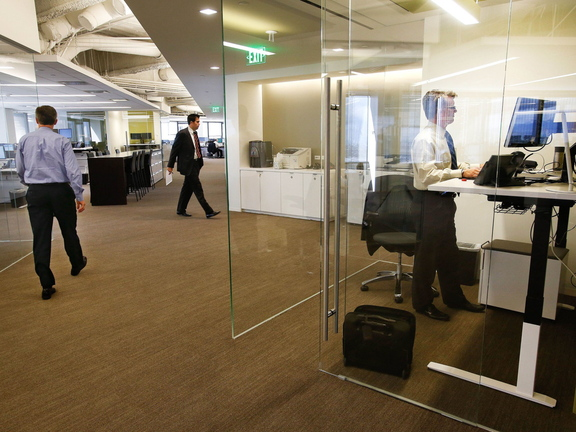 Paul Steitz, right, a senior vice president at the CBRE Group, works inside a focus room at the company's new headquarters.