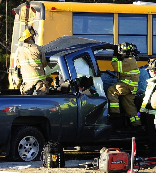 Emergency crews remove the roof of a pickup truck as they work to free the driver at the scene of a crash involving an Augusta school bus Tuesday on Riverside Drive just south of Stevens Road in Augusta.