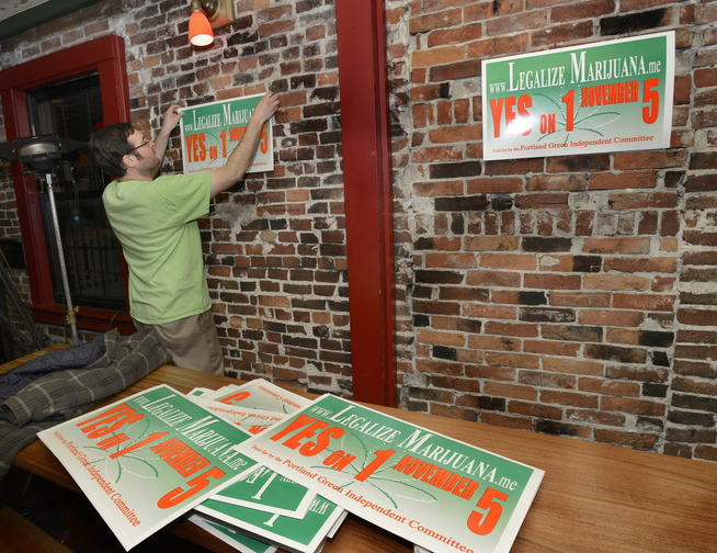 Yes on 1 campaign manager Tony Zeli hangs posters inside Brian Boru where they plan to celebrate a win.