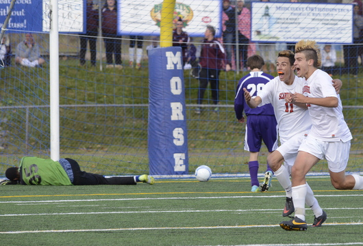 Sam Ware (11), who scored the overtime goal Saturday that gave Scarborough the Class A boys' soccer state championship, celebrates with Charlie Mader after the 2-1 victory against Hampden Academy in Bath. There was no celebrating for the fallen Hampden goalkeeper, Isaiah Bess, who time after time had come up with huge saves – 21 for the game – to keep the Broncos in it.