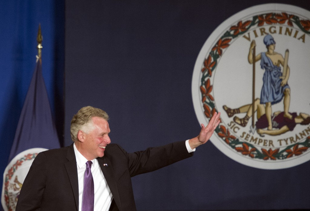 Va. Governor-elect Democratic Terry McAuliffe waves next to the flag of Virginia as he appears onstage to address his supporters at his victory party in Tysons Corner, Va., Tuesday, Nov. 5, 2013.