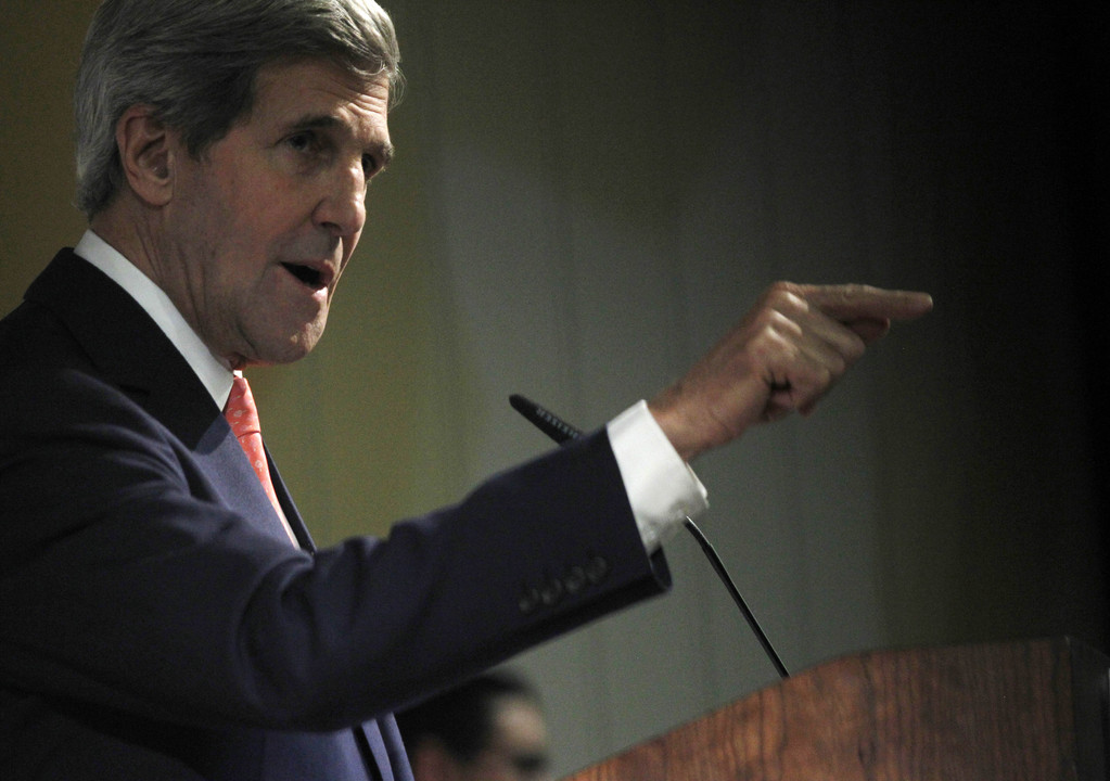 U.S. Secretary of State John Kerry gestures Sunday in Dubai while discussing the latest round of negotiations seeking to limit Iran's uranium enrichment.