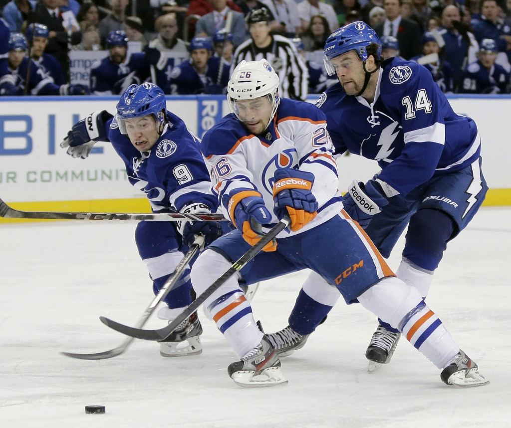 Edmonton center Mark Arcobello slips between Tyler Johnson, left, and Brett Connolly of Tampa Bay during the first period of Thursday's game in Tampa, won by the Lightning, 4-2.
