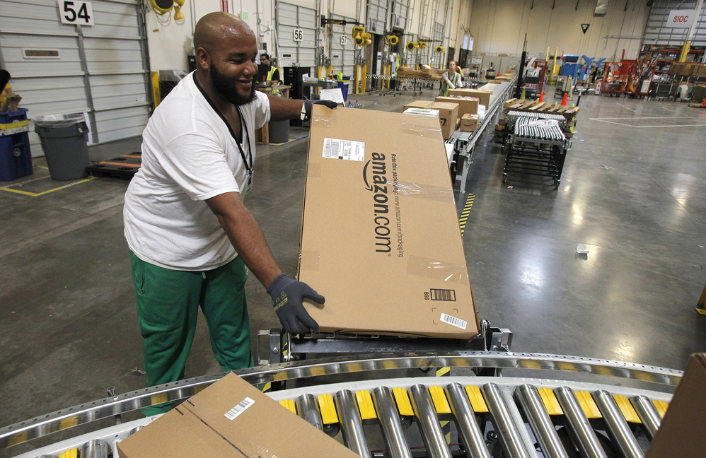 Leacroft Green places a package on the belt at an Amazon.com fulfillment center in Goodyear, Ariz. Amazon is teaming up with the U.S. Postal Service to deliver packages on Sundays. The service will debut in New York and Los Angeles.