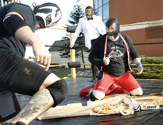 Jacob Cote and Antoine Malaab argue about who won their pizza party wrestling match after they both slammed each other onto the pizza at the Coast City Comicon convention at the Double Tree Hilton in South Portland on Saturday. Both were declared winners.
