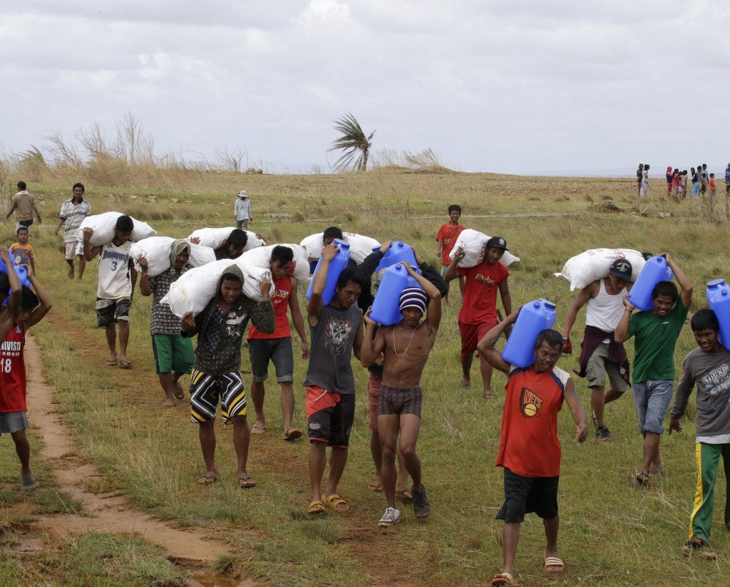 Survivors carry relief supplies unloaded by a U.S. Navy helicopter Saturday to villagers isolated by last week's typhoon Haiyan on Manicani island in the Philippines.