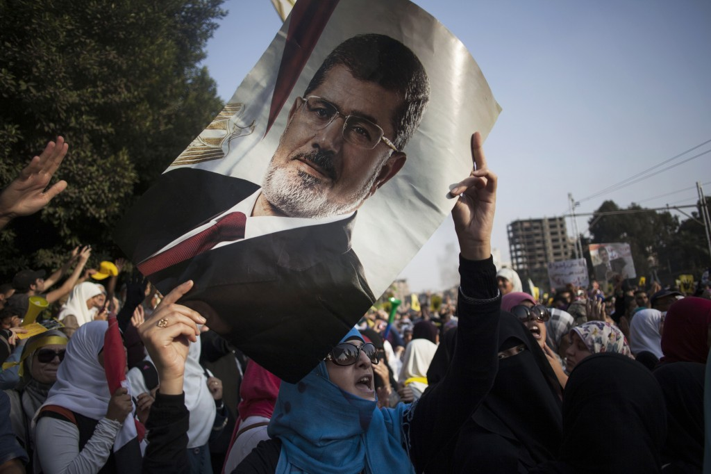 An Egyptian woman holds a portrait of ousted Egyptian President Mohammed Morsi during a protest Friday in Cairo. The trial of Morsi opens Monday, presenting serious challenges for the military-backed authorities. Days before the trial, the location of where he will be tried has not been announced for security reasons. His supporters threaten massive protests that may disrupt the proceedings. And in his anticipated first public appearance after four months in secret military detention, Morsi could turn his trial on charges of inciting murder into a platform for indicting the coup, giving more vigor to the opposition.