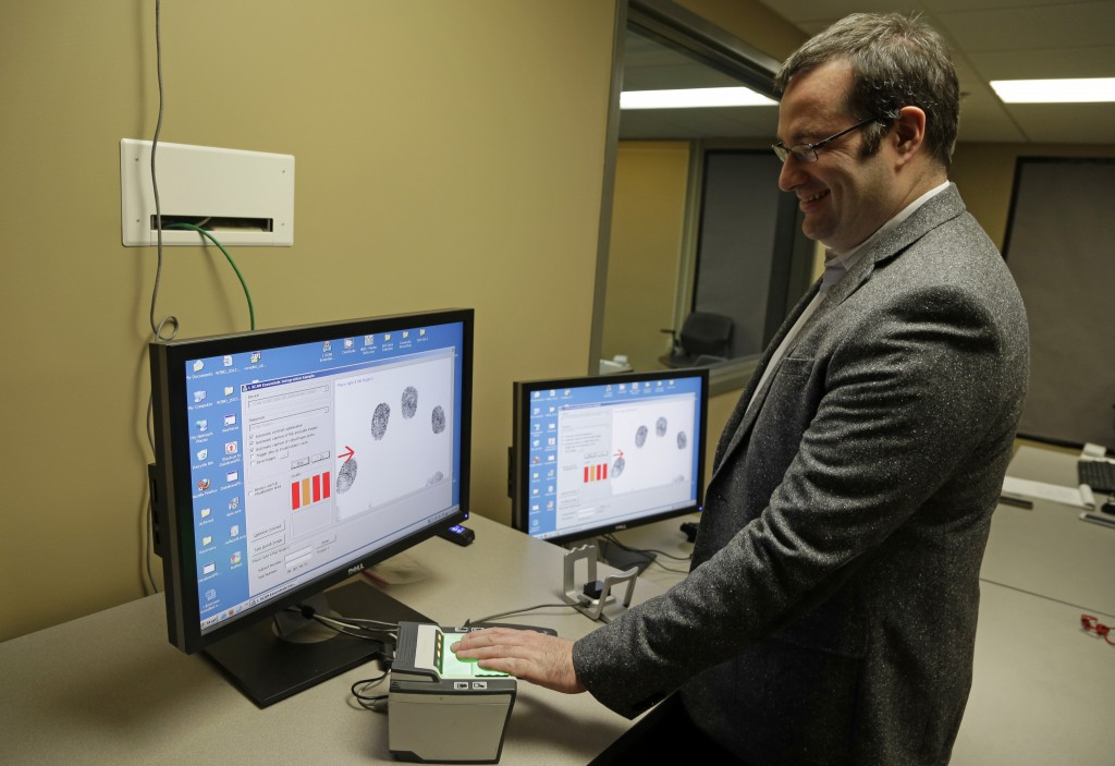 Stephen Elliott, director of international biometric research at Purdue University, demonstrates a fingerprint recognition system at one of his biometric labs last month in West Lafayette, Ind. Automated recognition of individuals based on their unique behavioral and biological characteristics is going mainstream and being studied by Elliott.