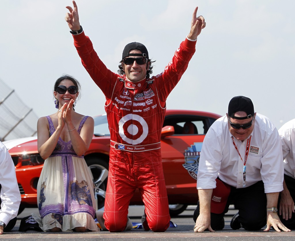 Dario Franchitti, center, of Scotland, celebrates at the start-finish line with his wife, Ashley Judd, and car owner Chip Ganassi, right, after winning the Indianapolis 500 at the Indianapolis Motor Speedway in Indianapolis in 2010.