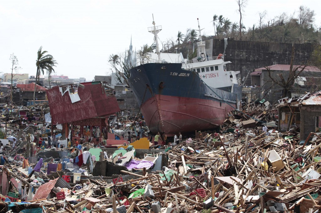 Survivors walk past a ship that lies on top of damaged homes after it was washed ashore in Tacloban city, Leyte province central Philippines on Sunday, Nov. 10, 2013. The city remains littered with debris from damaged homes as many complain of shortage of food, water and no electricity since the Typhoon Haiyan slammed into their province. Haiyan, one of the most powerful typhoons ever recorded, slammed into central Philippine provinces Friday leaving a wide swath of destruction and scores of people dead.