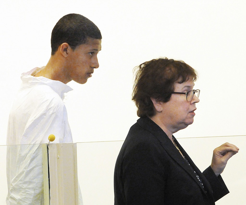 In this Oct. 23, 2013 file photo, Philip Chism, 14, stands during his arraignment for the death of Danvers High School teacher Colleen Ritzer, as his attorney Denise Regan speaks on his behalf in Salem District Court in Salem, Mass. In an indictment returned Thursday, Nov. 21, 2013, Chism was charged with sexually assaulting and killing Ritzer, and stealing her credit cards and iPhone.