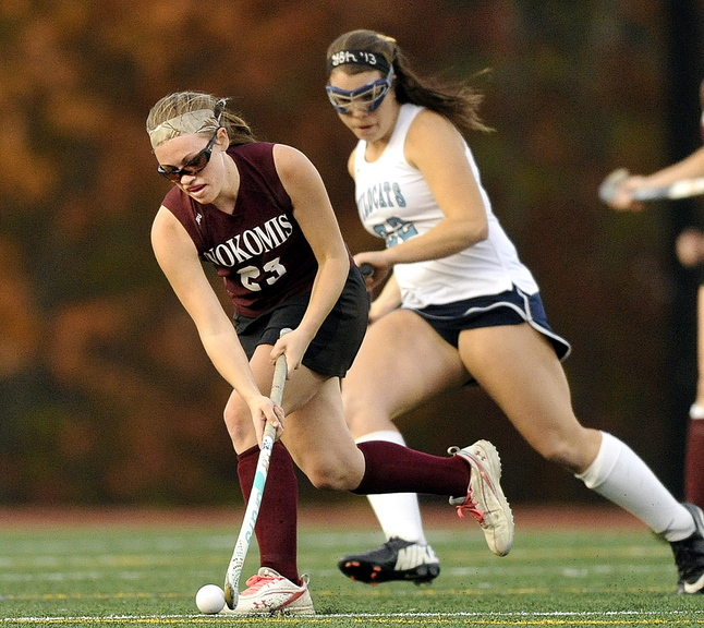 Taylor Shaw of Nokomis moves with the ball in front of York's Madeline Leroux during first half action in the Class B field hockey championship at Yarmouth High School Saturday, November 2, 2013.